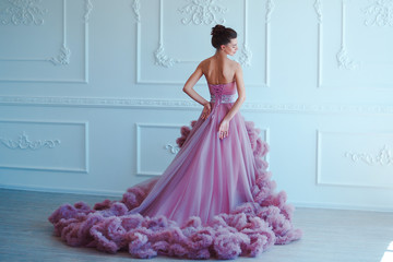 Beauty brunette model woman in evening purple dress. Beautiful fashion luxury makeup and hairstyle. Seductive girl silhouette in classic interior.