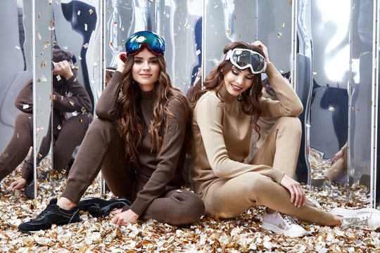 Two beautiful woman friends sit on the floor mirror sequins party fun celebrate new year holiday wear casual knitted wool suit ski goggles sport shoes extreme winter game brunette heath lifestyle.