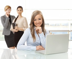 Smiling woman with laptop at office