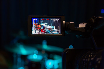 The LCD display on the camcorder. Filming the concert. Drum set and bass.