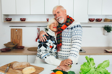 elderly couple embracing in the kitchen, seniors people spending time together at home.