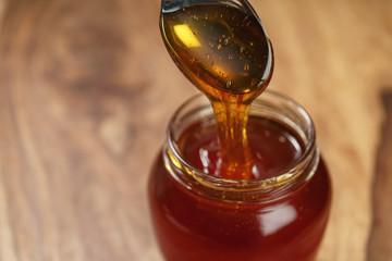 organic honey drips from spoon in jar