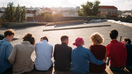 Group of diverse young students sitting on the roof top. Unity teamwork leisure communication