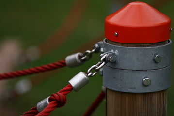 Wooden pole with fixed red ropes attached with metal clamps on playground for protection and attachment