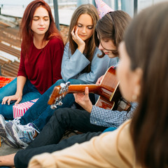 Girls listen to boy playing guitar. Art music lifestyle. Captivating sounds of romantic performance