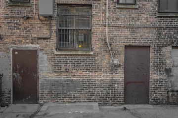 Brick wall with brown doors and barred window