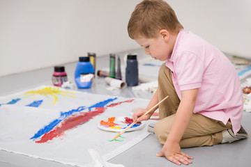Cute kid boy sitting on the floor and drawing with colorful paints.Child making flag craft. Education, creativity and school activities.