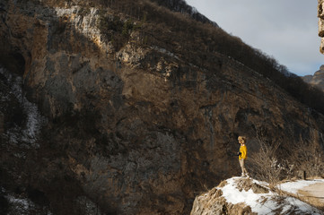 A girl photographer in sunglasses and a big fur hat and a yellow knitted sweater stands against the background of high rocks in the gorge with a dslr camera on her neck.