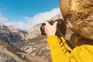 Close up A girl photographer in a fur hat and a yellow sweater in the mountains takes pictures on her digital camera.