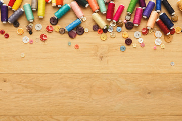 Collection of threads and buttons on wooden table background