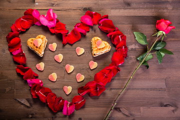 On the wooden table there is one pink rose and a heart of rose petals, inside of which are cookies in the form of hearts. View from above