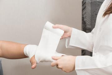 Doctor bandaging to upper limb of  man.