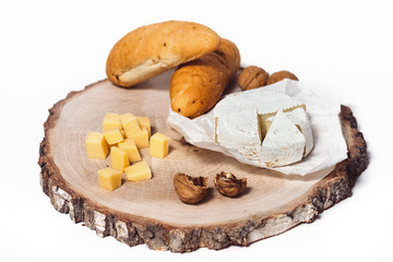 Cheese Camembert, bread, nuts and fruit on old wooden board. Food for wine and romantic, cheese and bread delicatessen isolated on white background...