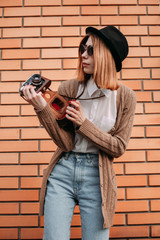 Fashionable young woman with a camera near a brick wall. warm colors