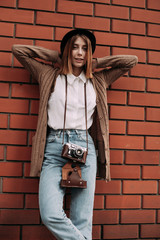 A young woman with a camera on a background of red bricks