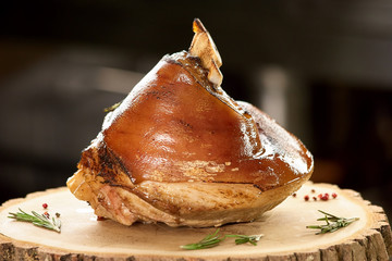 Pyramid shaped pork knuckle. Pyramid shaped roasted pork dish on wooden table.