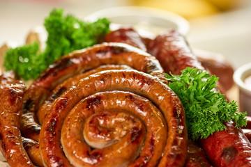 Juicy spiral sausage coil in pile, closeup. Juicy spiral sausage coil and parsley.