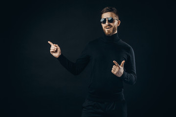 Handsome bearded man in black and flip-up sunglasses smiling and pointing away on black.