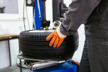 Auto mechanic taking tire.