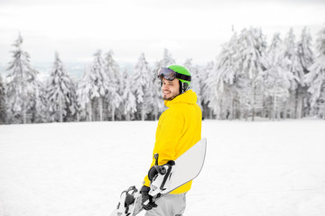 Man in winter sports clothes walking with snowboard at the snowy mountains