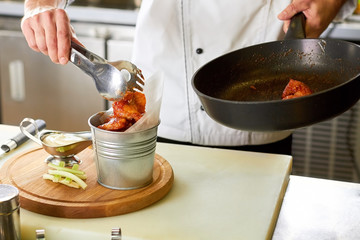 Hot chicken wing bucket filling using kitchen utensil tongs. Chef transfering chicken pieces from pan to metal bucket.