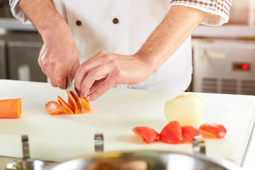 Cooker man slicing carrot using knife. Chef hands using knife. Slicing action.