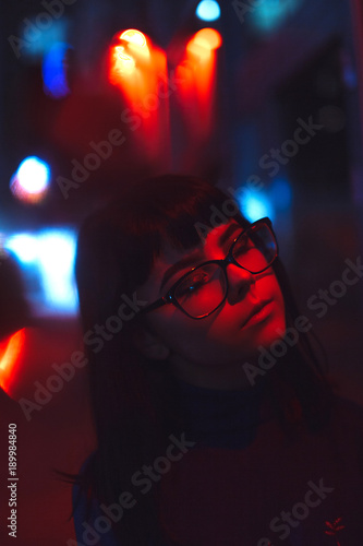 Young Japanese girl stand near neon lights and pose to the