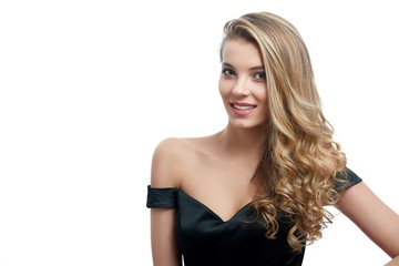 Portrait of a beatiful smiling girl with blonde curly hair in a nice evening dress with an open top. Photo was made on the white studio background. She looks gorgeous