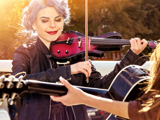 Music on violin by woman perform in park outdoor. Girl performing jazz on city street. Color tone on shiny sunlight background. Spring outside with blue hairstyle background. Toning of spring photo.