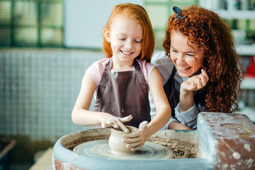 redhead mother and daughter mold with clay on pottery