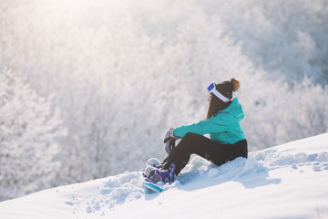 Woman snowboarder sitting on high hill and rest