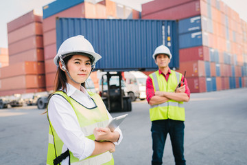 Staff and foreman control loading container cargo in logistic, export, import industry with forklift and container cargo freight in background.