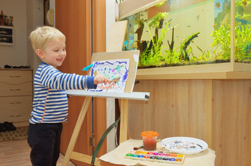 A little boy paints on an easel at home.