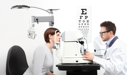 optometrist examining eyesight  patient in optician office on white background
