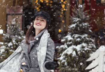 Beautiful stylish girl wears black cap and grey coat having fun with first snow before garland trees, snowy city christmas outdoor shot