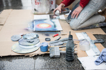 Spray paint show for audience in the middle of the street, set of working tools, workflow in the background, art