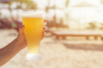 Hand of a man holding a glass of beer on the beach