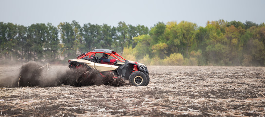 Quad bike with an men at the wheel rushes through the field in t