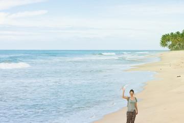 Balapitiya Beach, Sri Lanka - A woman waving her hand at the beach of Balapitiya