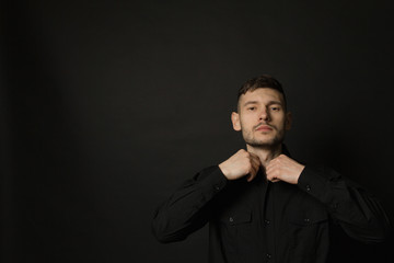 Handsome and positive guy in a black shirt on a black background