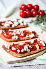 Homemade traditional italian snack Bruschetta with cherry tomatoes, salted feta cheese and thyme on a wooden cutting board, selective focus