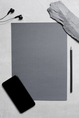 Workplace with gray textured sheet of paper and black smartphone