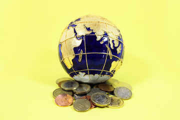 Blue and gold globe sitting on top of a pile of a mixture of coins from the US Europe and Britain