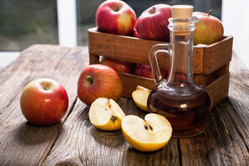 Apple cider vinegar  and apples on a wooden table