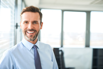Portrait of happy businessman smiling at office