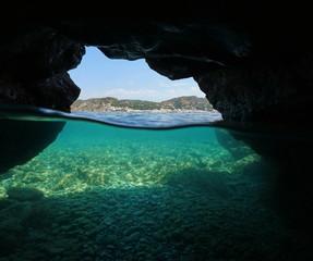 Over and under the sea inside a cavern on the seashore with the Mediterranean village El Port de la Selva and pebbles underwater, Spain, Costa Brava, Girona, Catalonia