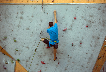 A teenager climbs up an artificial rock wall