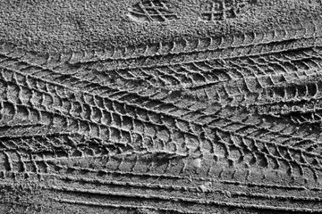 Tyre tracks on sand in black and white.
