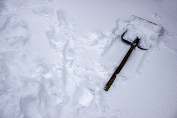 The snow shovel lies on the white snow. Footprints in the snow in winter.