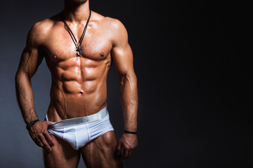 Muscular and sexy torso of young man with perfect abs in panties.